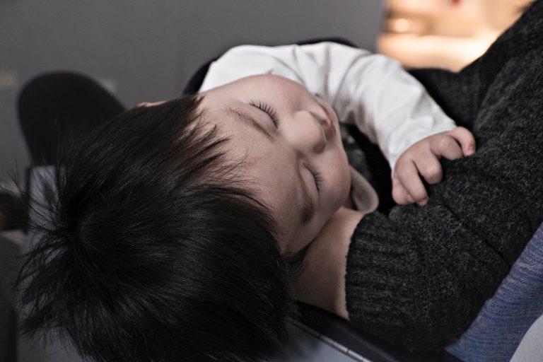 baby sleeping on father's lap - JoAnna Inks Sleep Solutions