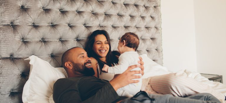 happy parents playing with baby - JoAnna Inks Sleep Solutions