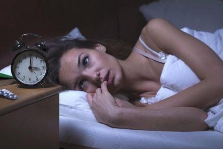 woman staring at alarm clock - JoAnna Inks Sleep Solutions
