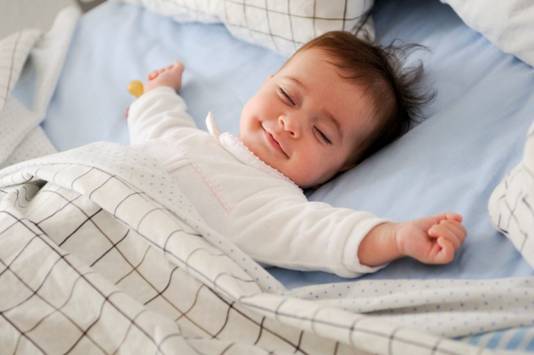 happy baby smiling in bed - JoAnna Inks Sleep Solutions