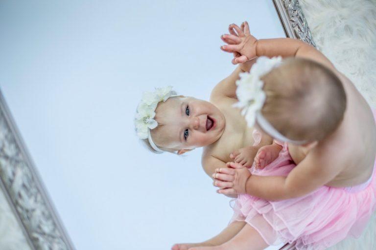 baby girl looking in a mirror - JoAnna Inks Sleep Solutions