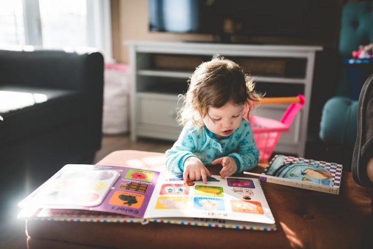 baby girl reading books - JoAnna Inks Sleep Solutions
