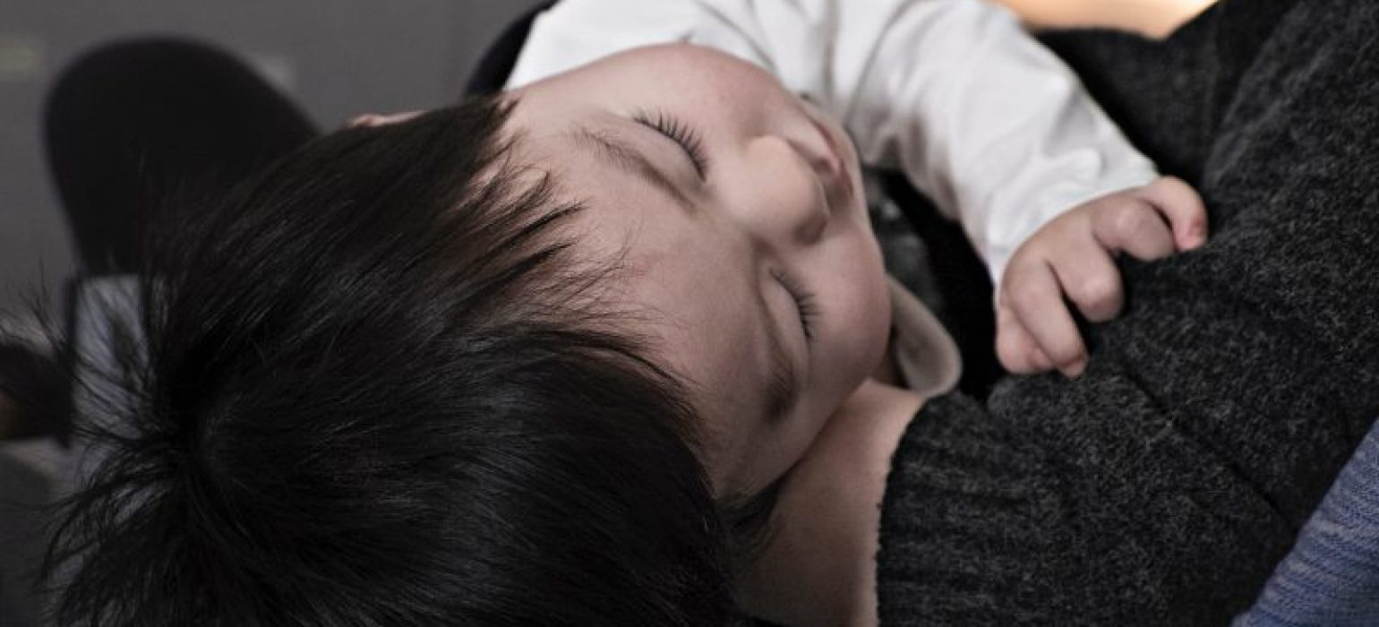 baby sleeping on father's lap - JoAnna Inks Sleep Solutions